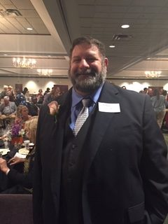 This image shows Dr. Guagliardo at the Cobb Chamber event recognizing him as Teacher of the Year from Life University.